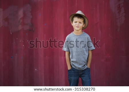 caucasian boy smiling wearing a hat in the park - stock photo