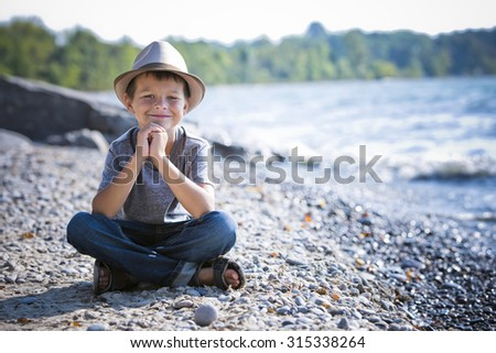 caucasian boy smiling wearing a hat on the beach - stock photo