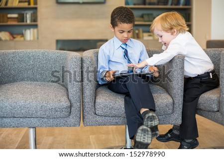 Caucasian boys and mulatto in the business clothing uses tablet in the business center - stock photo