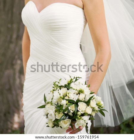 Caucasian bride holding wedding bouquet of various flowers.