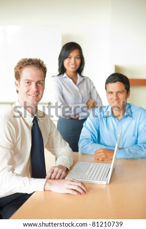 Caucasian British businessman sitting at conference room desk leading diverse team meeting with a handsome Latino male and beautiful Asian female, smiling and looking at camera. Vertical copy space