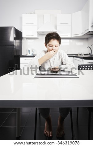 Caucasian brunette boy in pajama eating cereal bites from the bowl while sitting at kitchen table - stock photo