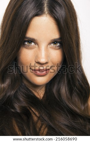 Caucasian brunette model with long wavy hair and perfect light skin. Toned in warm colors, Cosmetics concept, vertical shot, studio - stock photo