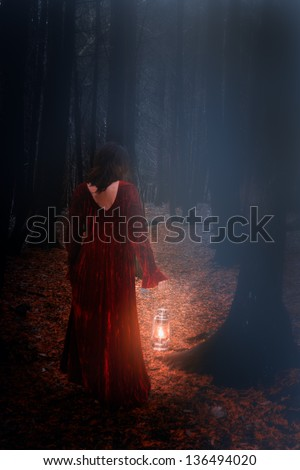 caucasian brunette woman in dark  scary woods with red velvet dress and lamp, walking away in circle of light, dark gloomy forest - stock photo