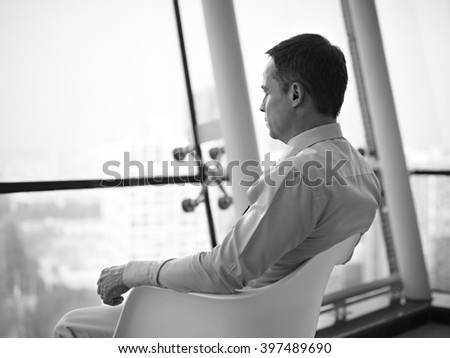 caucasian business executive sitting by the window in a chair thinking in office, black and white. - stock photo