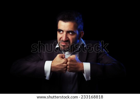 Caucasian business man in suit being angry, thinking to revenge against black background - stock photo