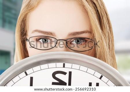 Caucasian business woman holding clock - stock photo