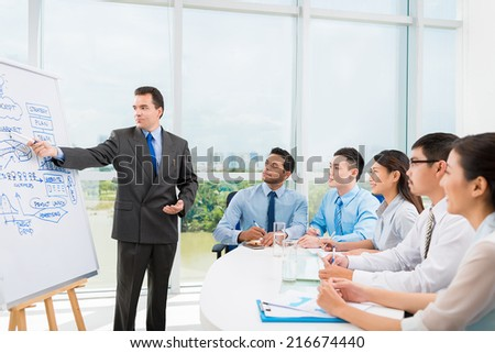 Caucasian businessman conducting training for his multi-ethnic employees - stock photo