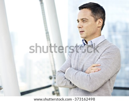 caucasian businessman in casual wear standing and thinking by the windows in office. - stock photo