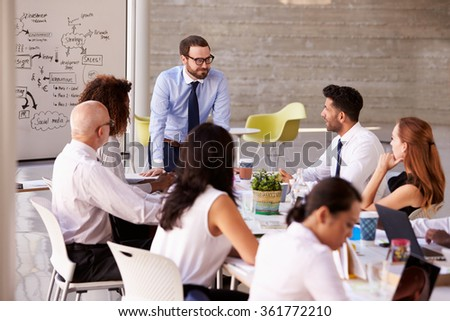 Caucasian Businessman Leading Meeting At Boardroom Table - stock photo
