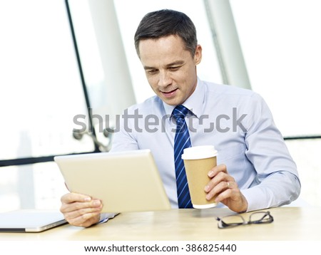 caucasian businessman looking at tablet computer holding coffee cup smiling in office. - stock photo