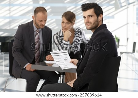 Caucasian businessman on meeting reading business report, looking back over the shoulder, smiling. - stock photo
