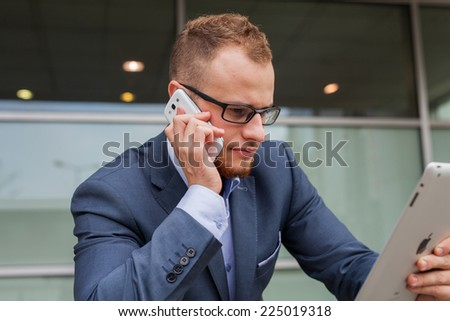 Caucasian businessman outside office using mobile phone and tablet pc on a office block background. Copy space. - stock photo
