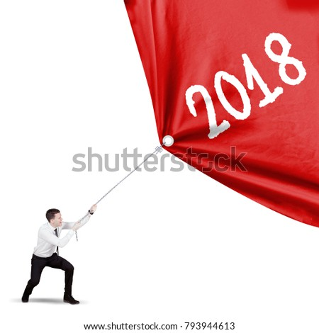 Caucasian businessman pulling a red banner with numbers 2018, isolated on white background