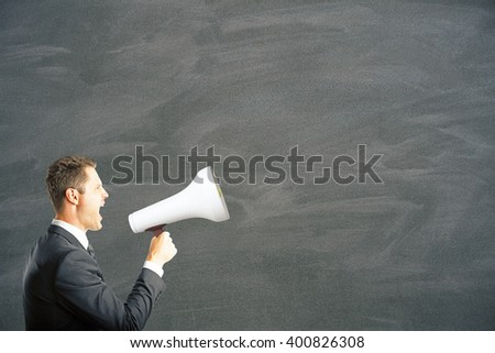 Caucasian businessman shouting into megaphone. Mock up - stock photo