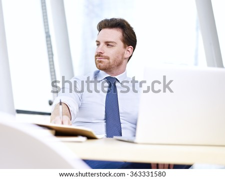 caucasian businessman sitting at desk in office looking away. - stock photo