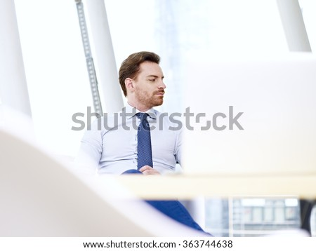 caucasian businessman sitting at desk thinking in office. - stock photo