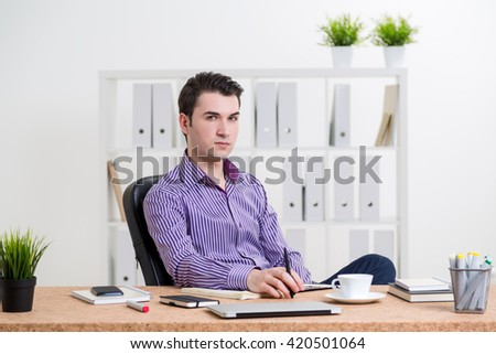Caucasian businessman sitting at desk with various items in office and looking at the camera - stock photo