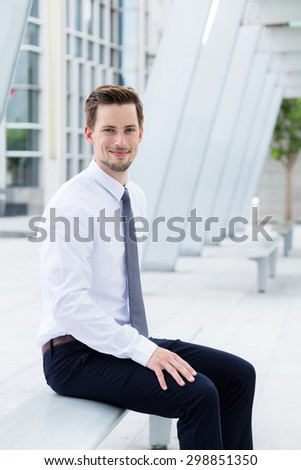 Caucasian businessman sitting on blench at outdoor