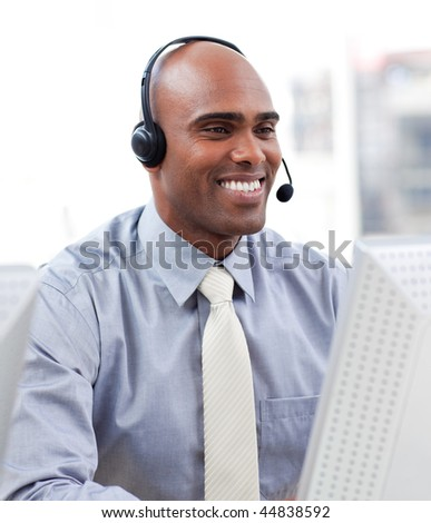 Caucasian businessman using a headset and a computer - stock photo