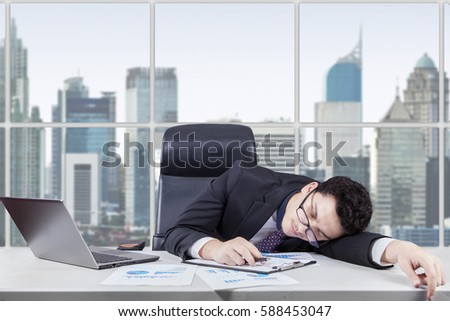 Caucasian businessman wearing formal suit and sleeping in the office with laptop and financial graph on the table