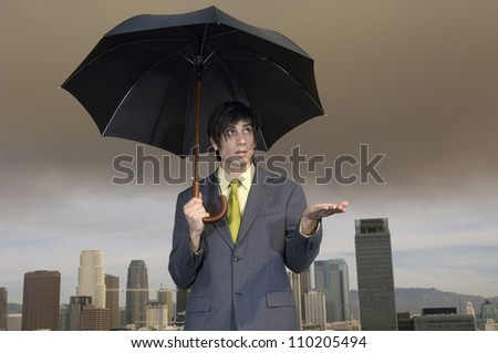 Caucasian businessman with an umbrella checking if its raining