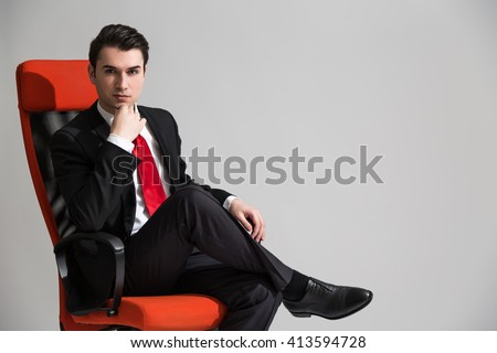 Caucasian businessman with hand at chin sitting on red swivel chair on grey background - stock photo