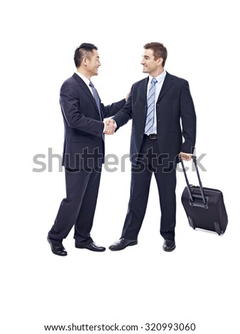 caucasian businessman with suitcase greeted by asian partner, isolated on white background. - stock photo