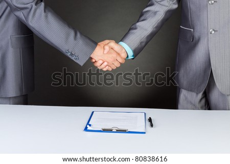 caucasian businessmen handshake after sign contract, in elegant suits over gray dark and business background, with clipboard, documents. Communication, greeting, agree, congratulation concept. - stock photo