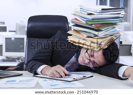 Caucasian businessperson sleeping in the office with documents on his head, shot in the office - stock photo