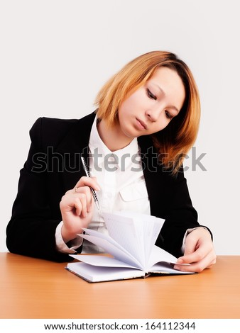 caucasian businesswoman sitting at desk in casual clothes and working with dayly log - stock photo