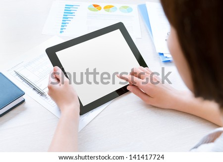 Caucasian businesswoman sitting at workplace and looking on blank modern digital tablet, touching on empty screen
