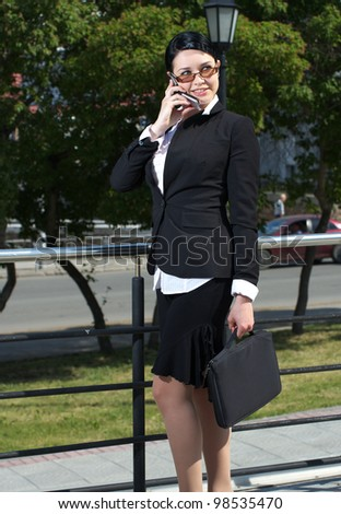 Caucasian businesswoman standing in the street and talking cellphone - stock photo