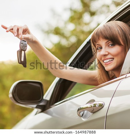 Caucasian car driver woman smiling showing new car keys and car. - stock photo