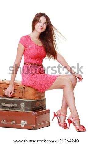 Caucasian charming young woman in a summer dress sitting on old suitcase isolated on white on a travel theme