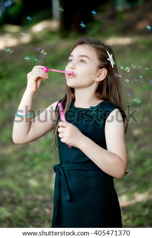 Caucasian child girl blowing soap bubbles outdoor