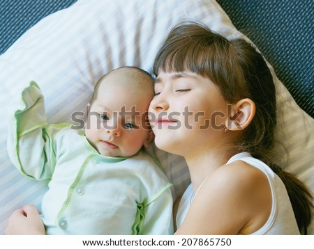 Caucasian child sister and baby brother lying together at home - stock photo