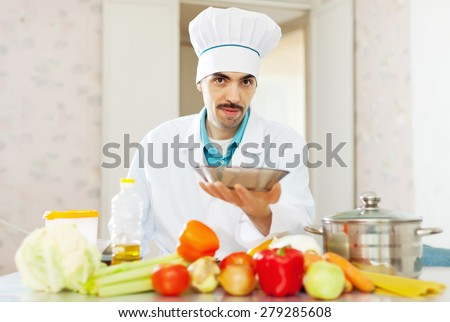caucasian cook in uniform with plate at kitchen - stock photo