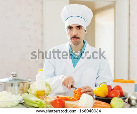 caucasian cook in white uniform does veggy lunch at kitchen - stock photo