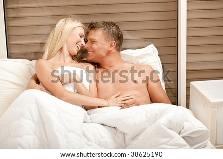 Caucasian couple embracing and enjioying in bed - stock photo