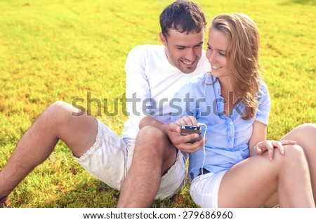 Caucasian Couple Sitting Together on the Grass Outdoors with palmtop Player. Listening to Music and Laughing. Horizontal Image Composition - stock photo