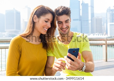 Caucasian couple use the cellphone together - stock photo