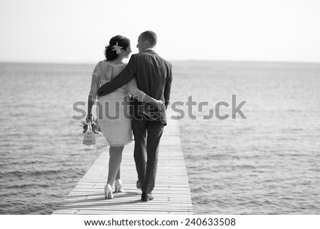 caucasian couple walking together on pier