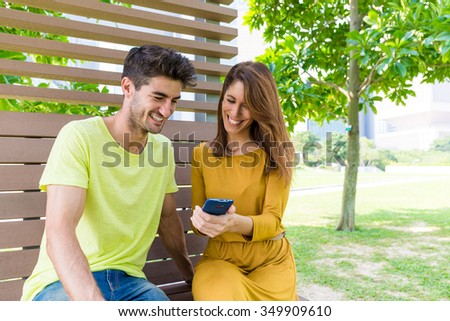 Caucasian couple watching the data on cellphone at park - stock photo