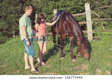 Caucasian couple with a brown horse in a countryside at summer