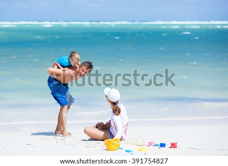 Caucasian couple with little son having fun on the beach