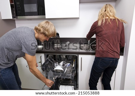 Caucasian couple working together in kitchen - stock photo