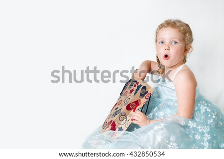 caucasian curly blond surprised girl in a ball gown in the New Year with Christmas snowflakes Christmas gift bags of brown paper in a pattern mittens christmas tree Christmas gifts in hands - stock photo