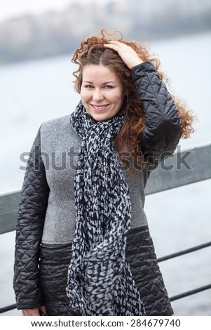 Caucasian curly hair woman looking at camera while standing on wind and holding hair - stock photo