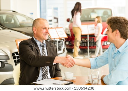 Caucasian customer and car salesman shaking hands - stock photo